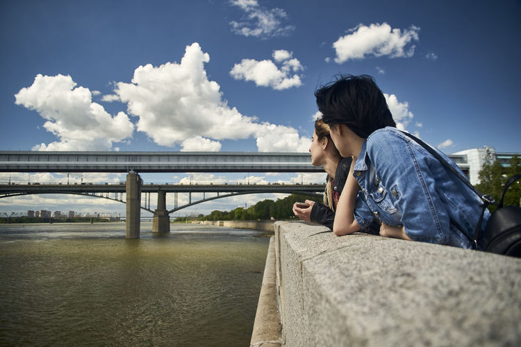 Women leaning on railing by river against sky