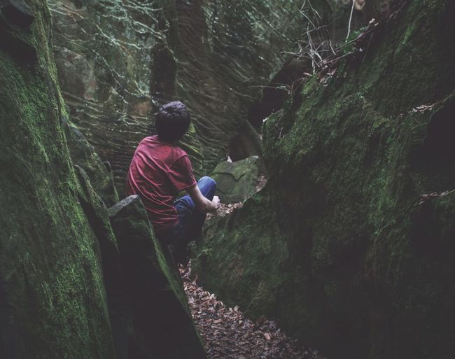 Rear view of man crouching amidst moss covered rocks