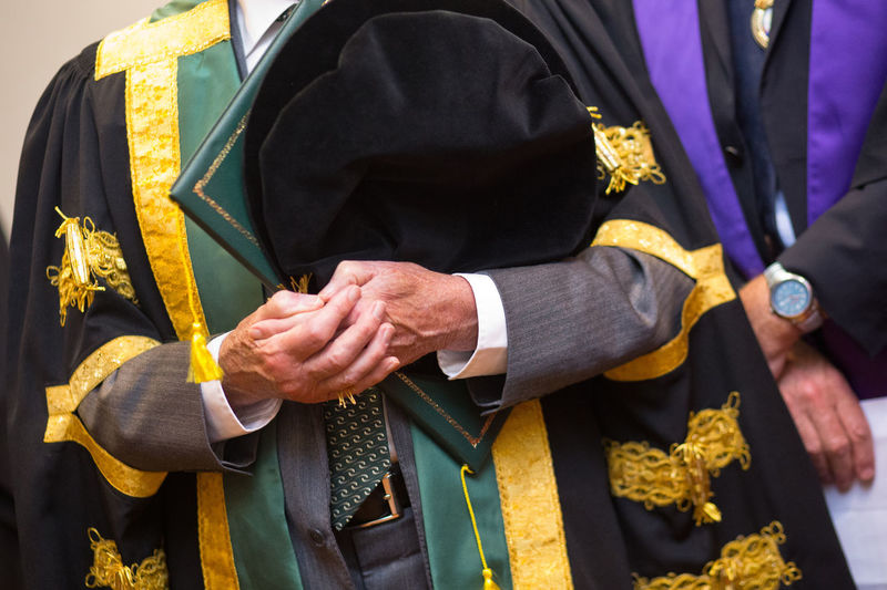 Midsection Of Man With Certificate Wearing Gown During Graduation Ceremony