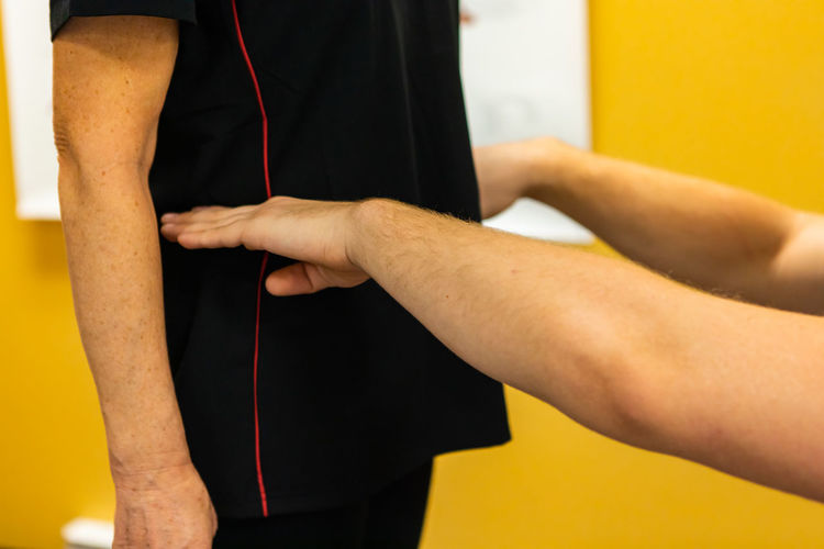 Cropped hands of physical therapist examining patient