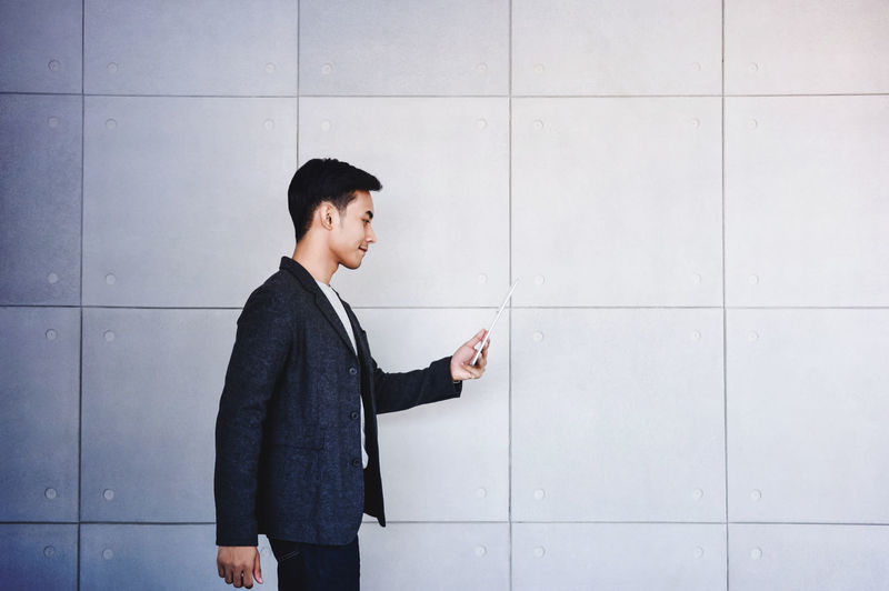 Side view of young businessman using mobile phone against wall