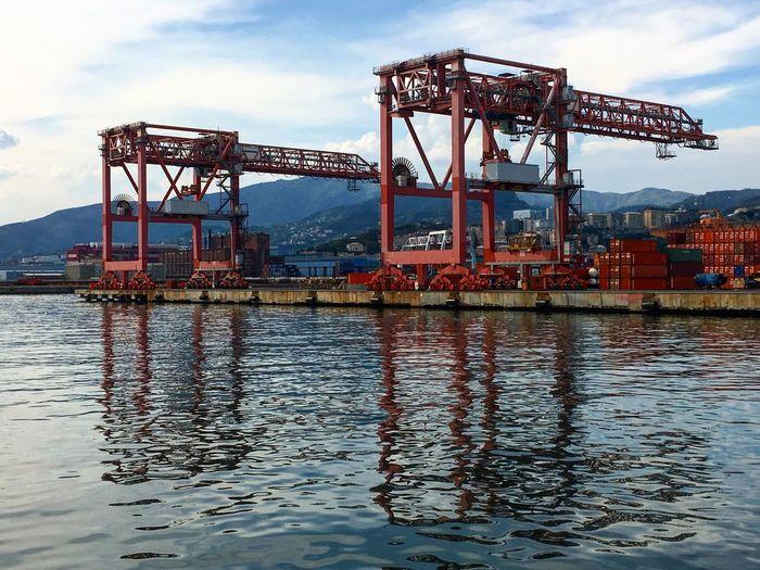 Cranes on dock yard in city against sky