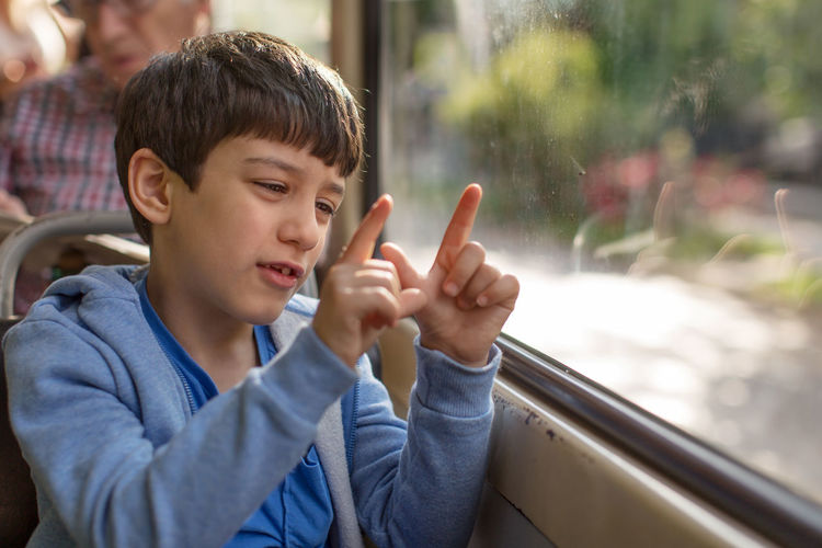 Young Boy Gesturing On A Bus