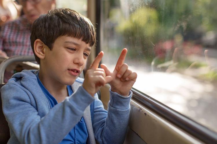 Boy sitting by window while gesturing in tram