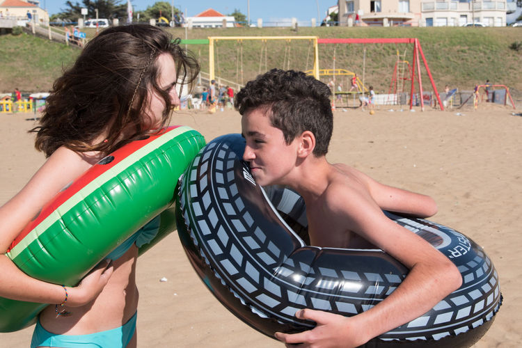 Side view of siblings with inflatable rings standing at beach during sunny day