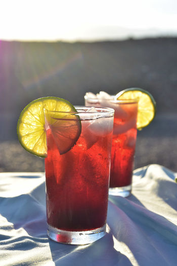 Cold drinks of iced tea made from hibiscus flower petal tea in hot desert setting