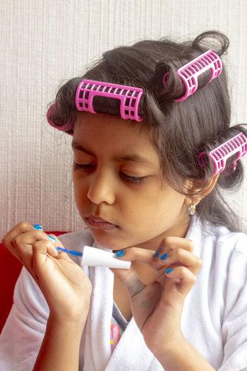 Close-Up Of Girl Applying Nail Polish While Sitting At Home