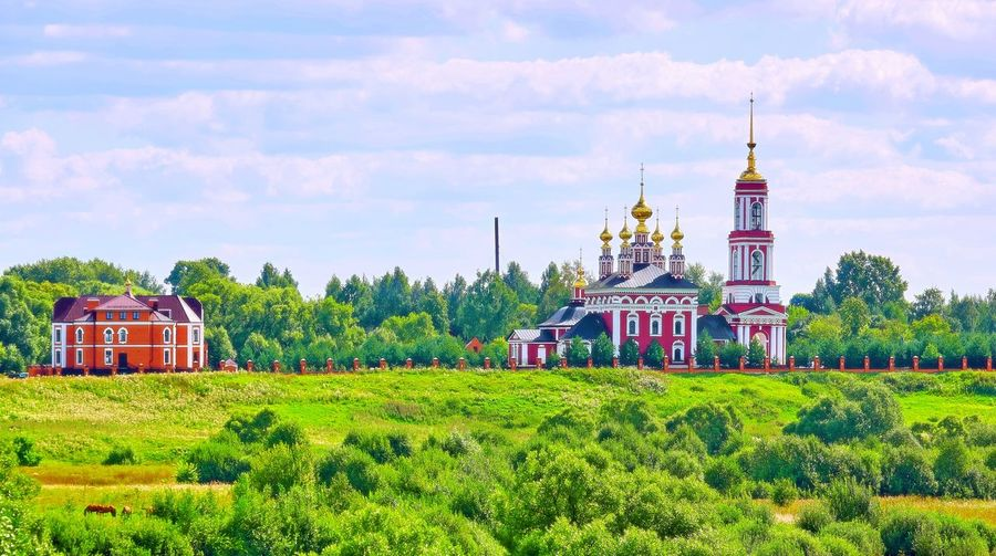 Vibrant view of orthodox church in sunny summer Suzdal Tranquility Summer Historic Famous Landscape Building Exterior Cloud Cloudscape Meadow Sunny Sunlight Tree Park Golden Cupola Orthodox Church Suzdal Christianity Green Red Sky Yellow City Sky Grass Architecture Cloud - Sky Shining Woods