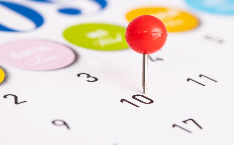 Close-up of thumbtack on calendar
