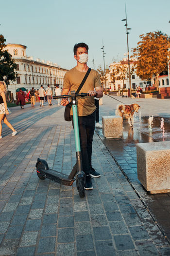 Young man riding an electric scooter in the city center. man wearing the face mask to avoid virus
