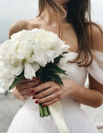 Midsection Of Bride Holding White Bouquet During Wedding Ceremony
