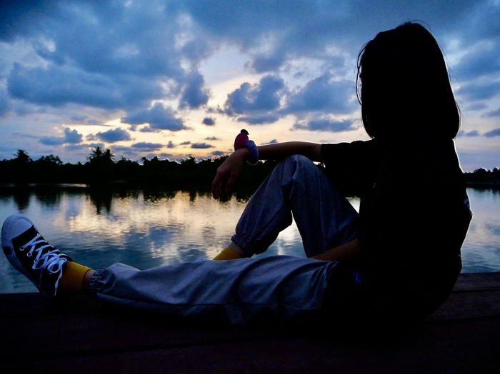 Man sitting by lake against sky during sunset
