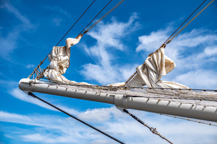 Low angle view of mast against cloudy sky