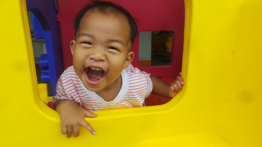 Portrait of cheerful boy playing at playground