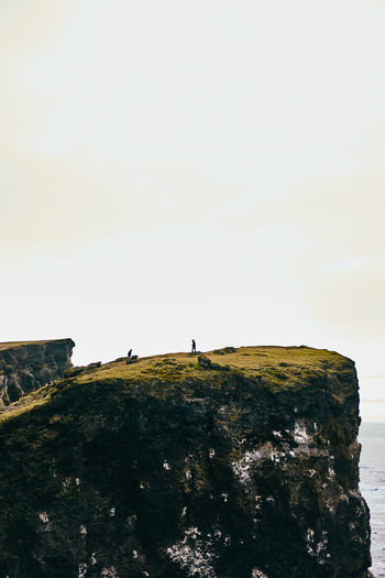 People standing on cliff by sea against sky
