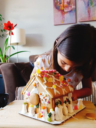 Girl Making Gingerbread House On Table At Home