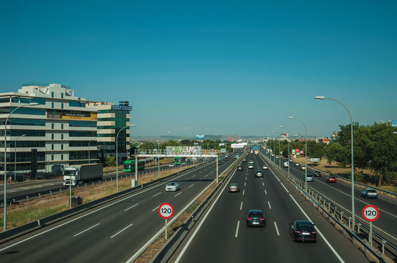 Vehicles on highway against clear sky