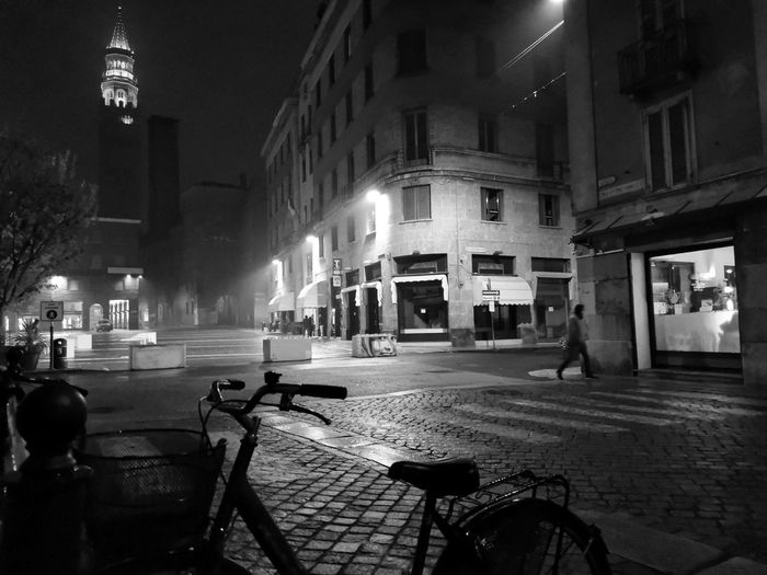 Empty street amidst buildings in city at night