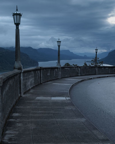 Decorative street lights on early cloudy and overcast morning at Vista House, Crown Point in Multnomah County, Sky Street Light Nature Transportation Architecture Lighting Equipment Mountain Built Structure Outdoors Road Street Diminishing Perspective Morning Overcast Mood Moody Sky Atmosphere Mystical Columbia River Gorge Columbia River Portland Oregon Vista Point Dusk River