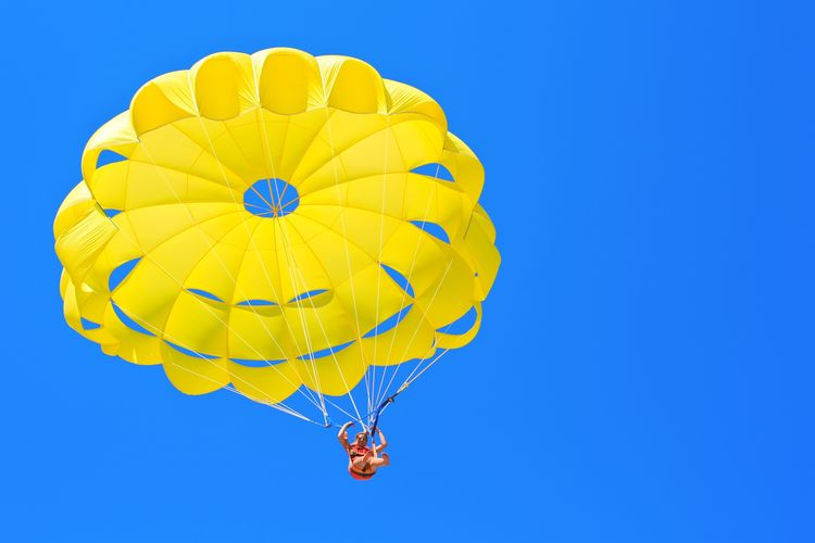 Low Angle View Of Woman Paragliding Against Blue Sky