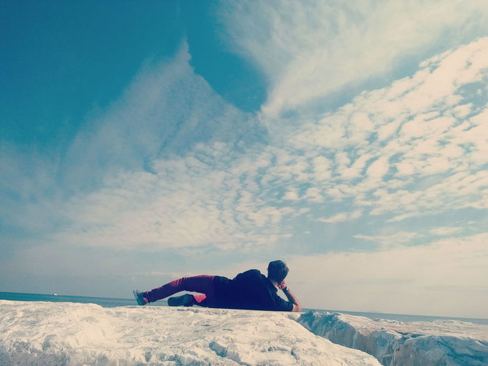 Rear view full length of man relaxing on rock against sky