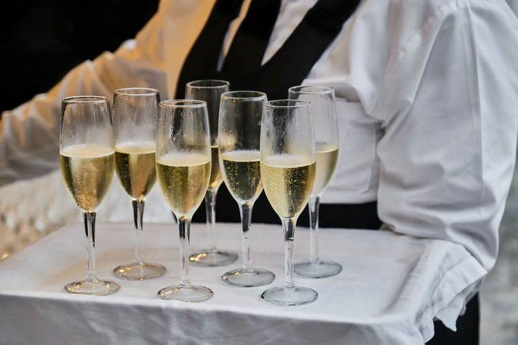 Midsection of waiter serving champagne on tray