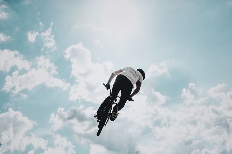 Low angle view of man performing stunt with bicycle against sky