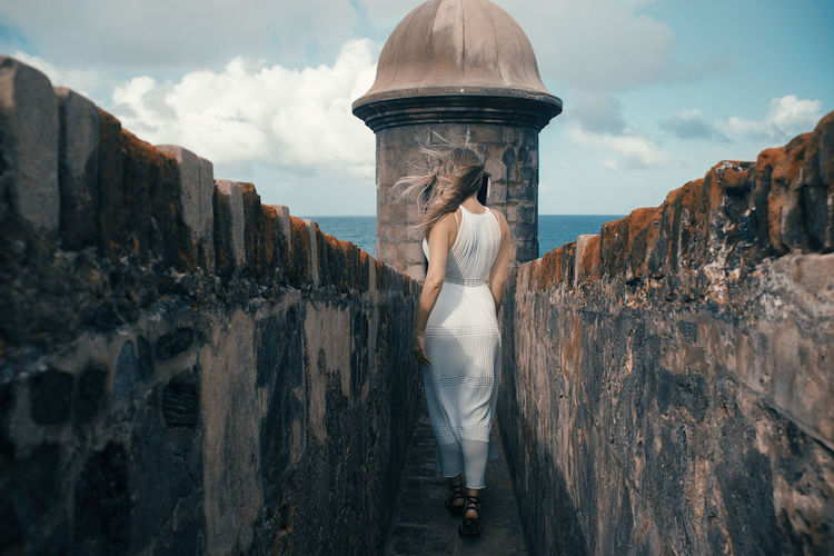 Rear view of woman walking amidst wall against sky