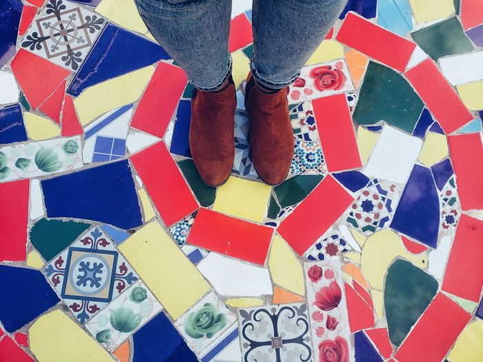 Low section of person standing on multi colored tiled floor