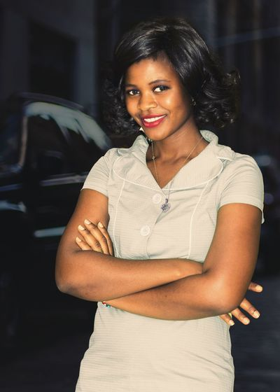 Portrait of young woman with arms crossed standing against cars at dusk