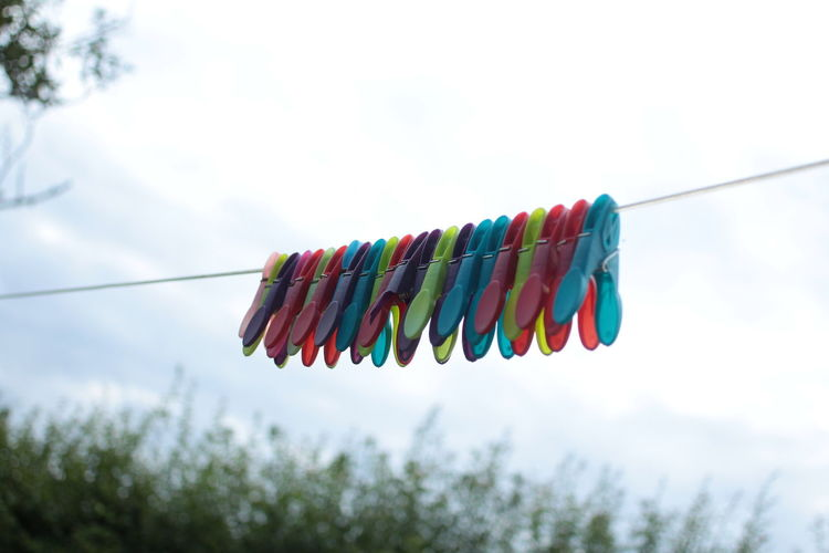 Low angle view of multi colored clothespins hanging against sky