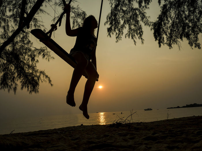 Silhouette girl swinging at beach against sky during sunset