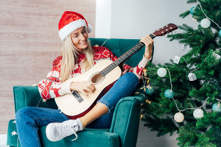 Full length of young woman playing guitar