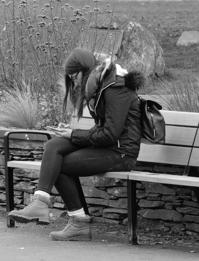 Street Photography People Photography Streetlife UK Black And White Monochrome Photography Young Adult One Woman Only Park Bench Sitting One Person Outdoors Dayout Grasses Verbena Bonariensis Stone Wall Plaque Mobile Phone Social Media