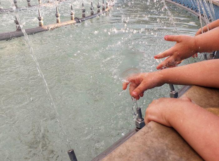 High angle view of hand splashing water in swimming pool