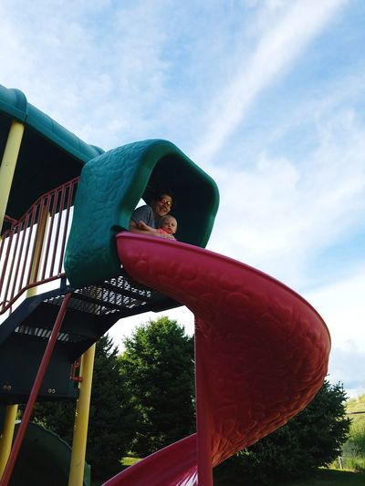 Low angle view of child in playground against sky