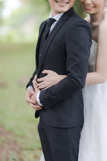 Midsection Of Bride And Bridegroom Embracing
