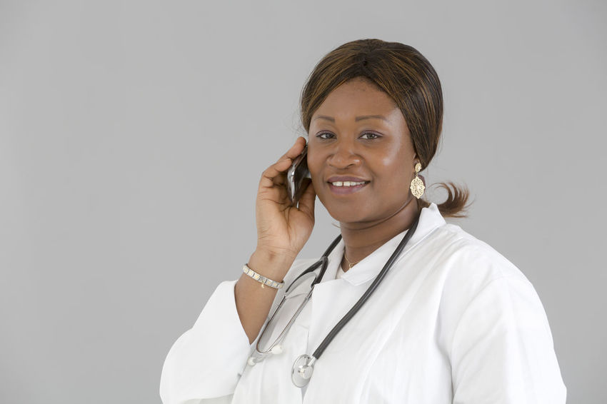 Medical Nurse Doctor  Hospital Pediatrics Pediatrician Clinic White Background Occupation Good News Reassurance Reassuring Beautiful Woman African Smiling Looking At Camera Looking To The Camera Portrait Front View Speaking On The Phone Talking On The Phone African Girl