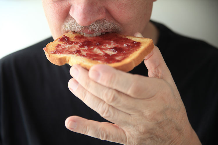 Midsection of man eating toast with jam against white background