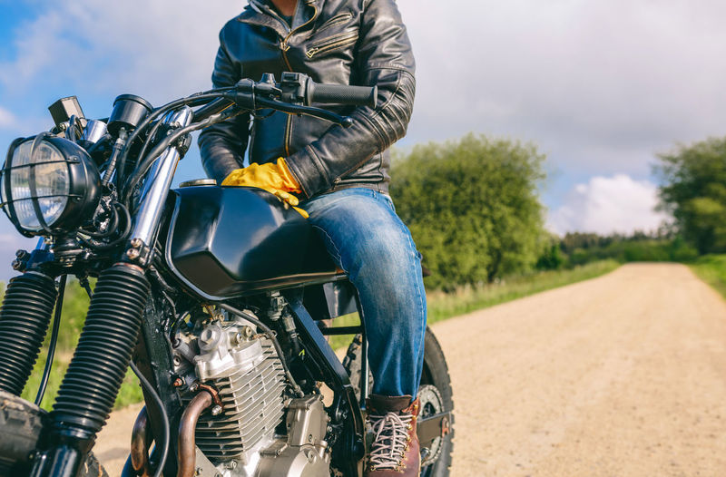 Low section of man sitting on motorcycle over road against sky