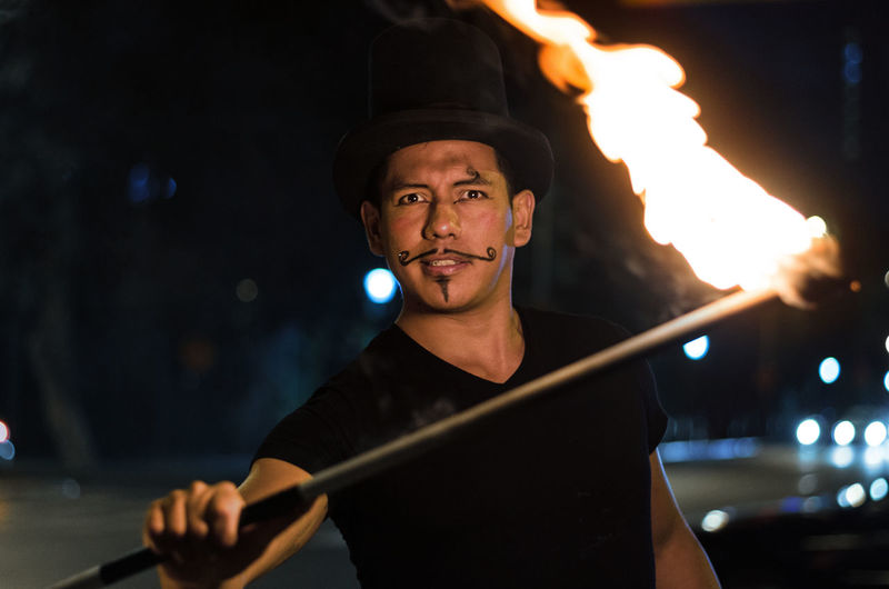 Portrait of man performing with fire on street at night