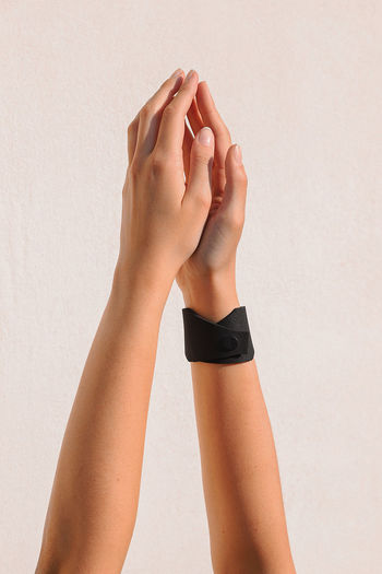 Midsection of woman holding hands against white wall
