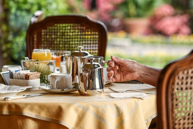 Midsection of woman preparing breakfast on table