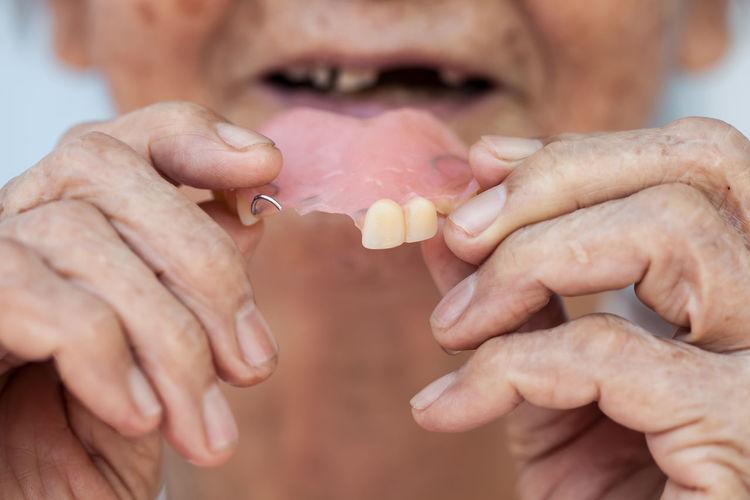 Cropped image of senior woman holding dentures