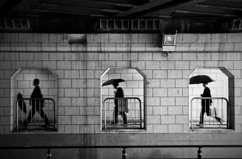Men walking on walkway under bridge