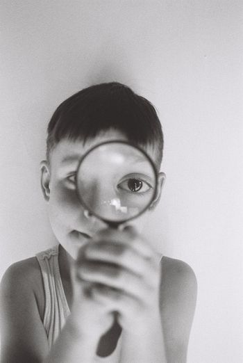 Portrait of boy holding magnifying glass against wall