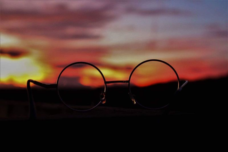 Close-up of sunglasses against sky during sunset
