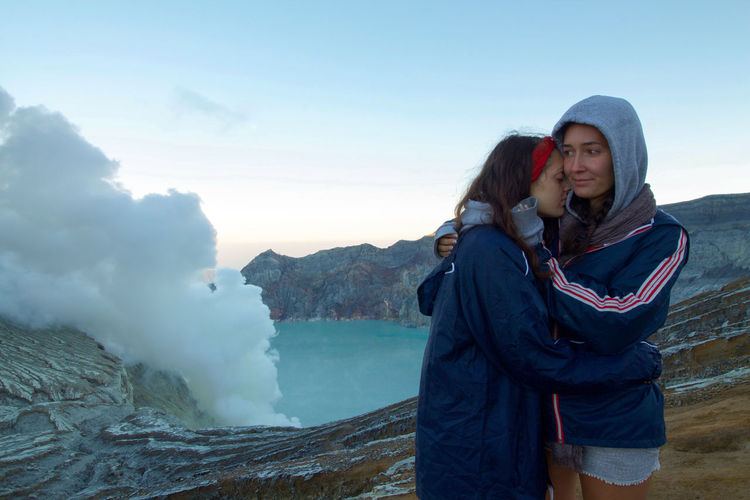 Sisters embracing against volcanic mountain