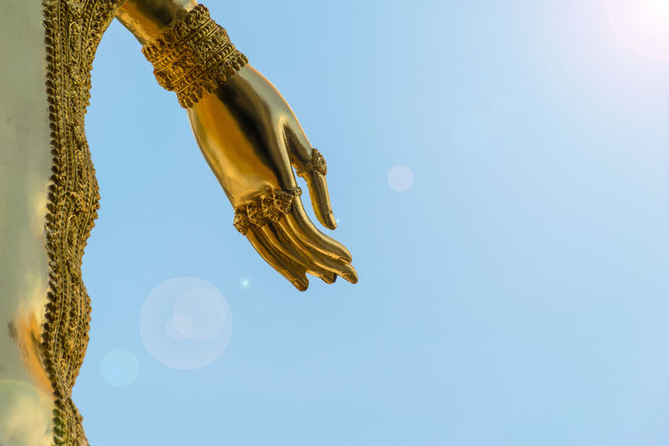 Buddha statue hand gold of Sky and sunshine Buddha Hope Thailand Beauty In Nature Blue Clear Sky Close-up Day Gold Colored Hand Low Angle View Nature Outdoors Sculpture Sky Spirituality Statue Sunlight
