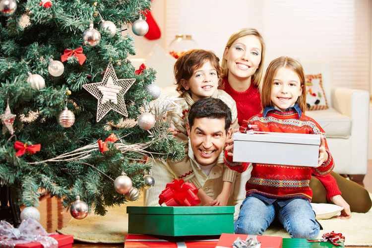 Portrait Of Smiling Family While Sitting By Christmas Tree On Sofa At Home